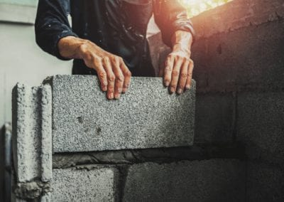 Man building a wall from cinder blocks